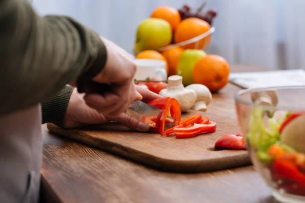 キッチンに赤ピーマンを切る男のトリミングされた画像 - ローフード ストックフォトと画像