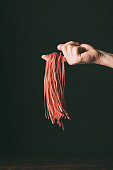 cropped image of man holding raw red tagliatelle on finger over table on black background