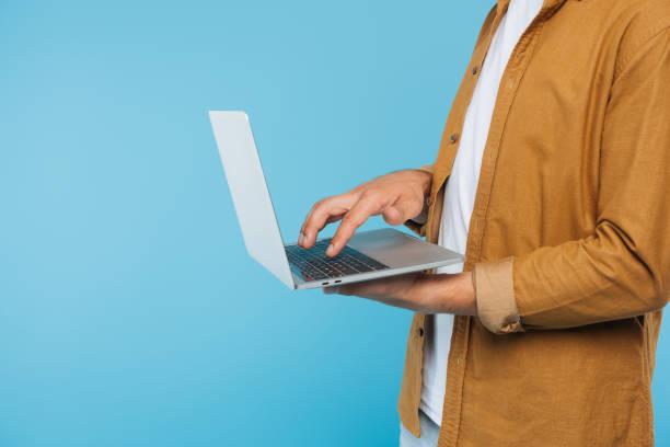zugeschnittenes Bild von Mann mit Laptop isoliert auf blau – Foto