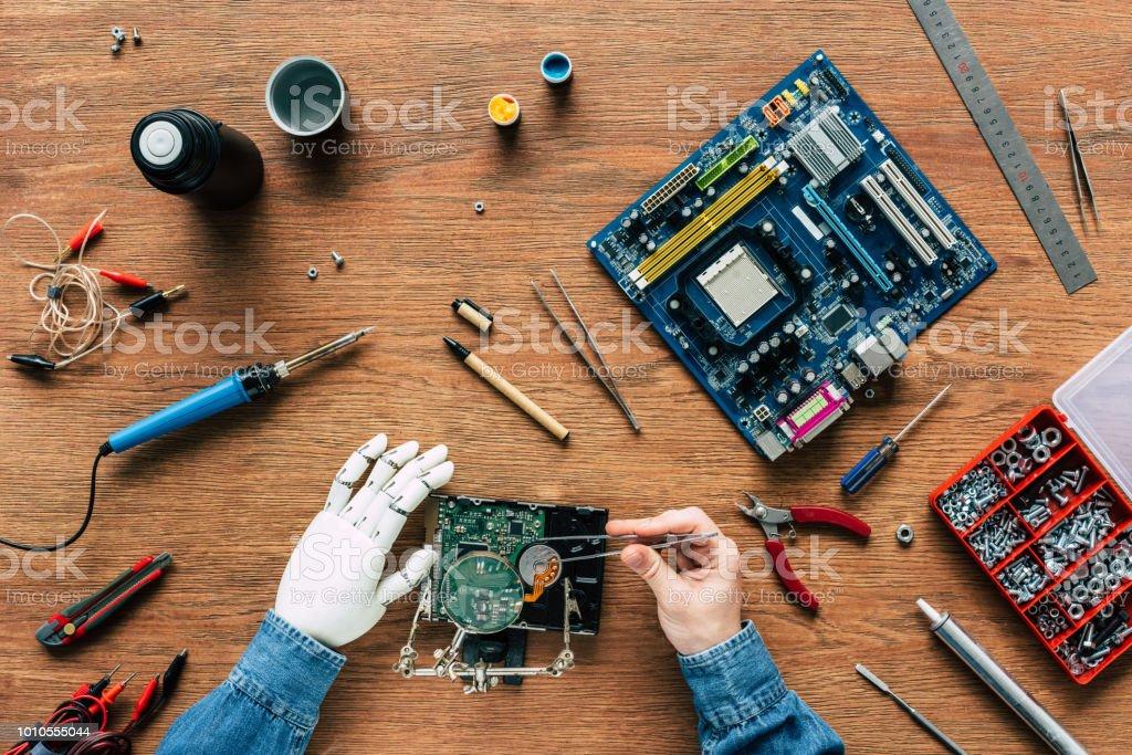 Bild des Mannes mit Roboterhand Reparatur Festplatte mit Pinzetten beschnitten – Foto