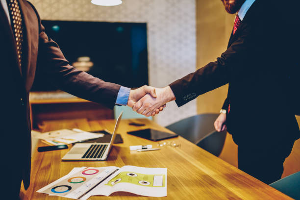 Cropped image of men in suits shaking hands making deal of sponsorship in business corporation, male entrepreneurs agree in partnership cooperation and contract during formal meeting in office stock photo