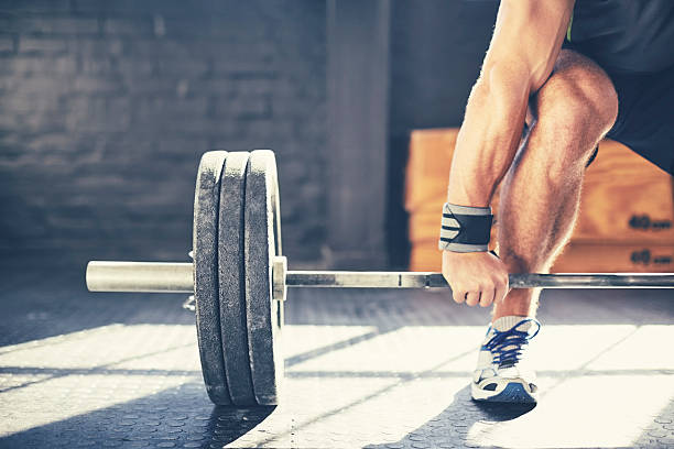 Cropped image of muscular man deadlifting barbell in gym stock photo