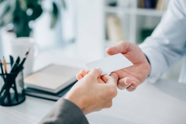 cropped image of patient giving empty card to doctor in clinic - identity card stock photos and pictures