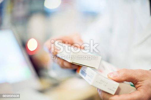istock Cropped image of pharmacist holding medicines 669895608