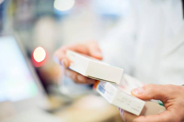 cropped image of pharmacist holding medicines - farmaco foto e immagini stock