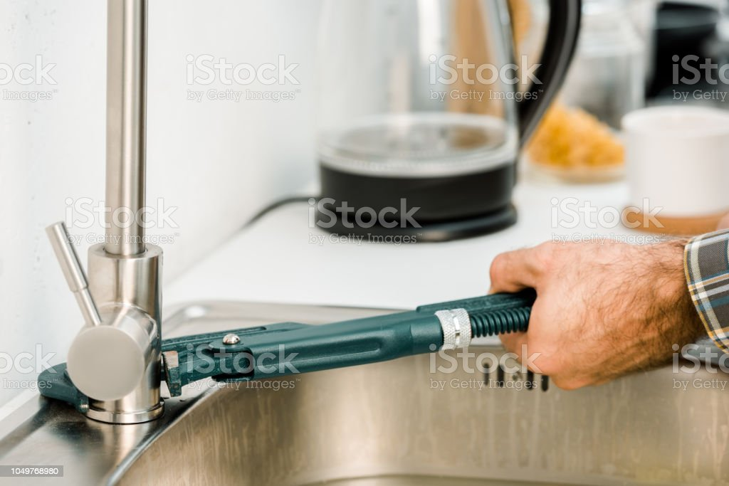 cropped image of plumber repairing tap with monkey wrench in kitchen