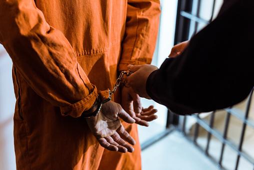 cropped image of prison officer wearing handcuffs on prisoner
