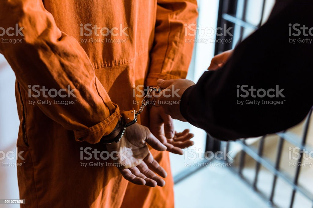 cropped image of prison officer wearing handcuffs on prisoner stock photo