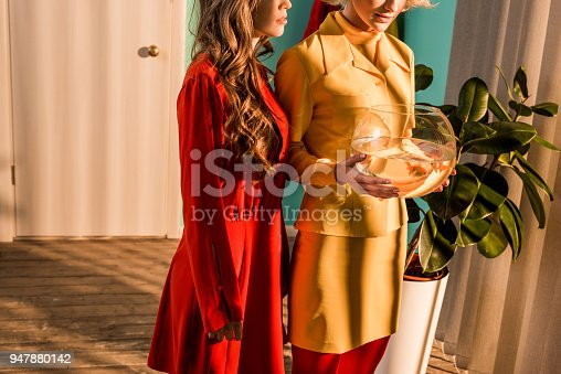 109350576 istock photo cropped image of retro styled girls in colorful dresses holding aquarium with fish at home 947880142