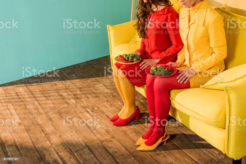 ブロッコリーを自宅のプレートと座っているカラフルなドレスでレトロなスタイルの女の子のトリミングされた画像 ストックフォト