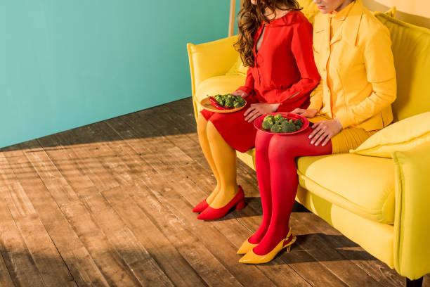 ブロッコリーを自宅のプレートと座っているカラフルなドレスでレトロなスタイルの女の子のトリミングされた画像 - ローフード ストックフォトと画像