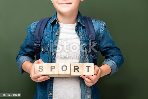 1016623732istockphoto cropped image of schoolboy holding wooden cubes with word sport near blackboard 1016623694