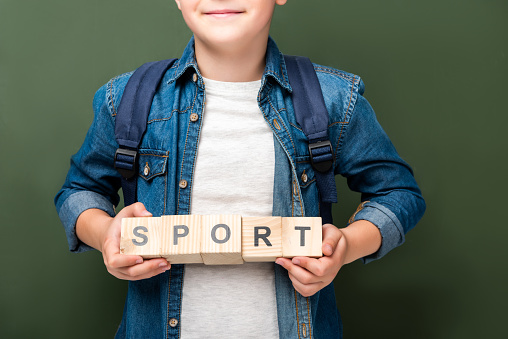 1016623732 istock photo cropped image of schoolboy holding wooden cubes with word sport near blackboard 1016623694
