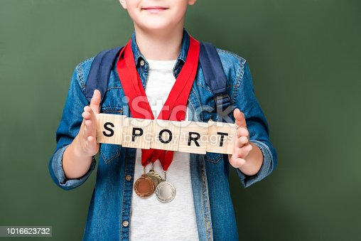 1016623732istockphoto cropped image of schoolboy with medals holding wooden cubes with word sport near blackboard 1016623732