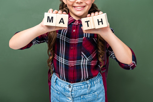 1016623732 istock photo cropped image of schoolchild holding wooden cubes with word math near blackboard 1016623640