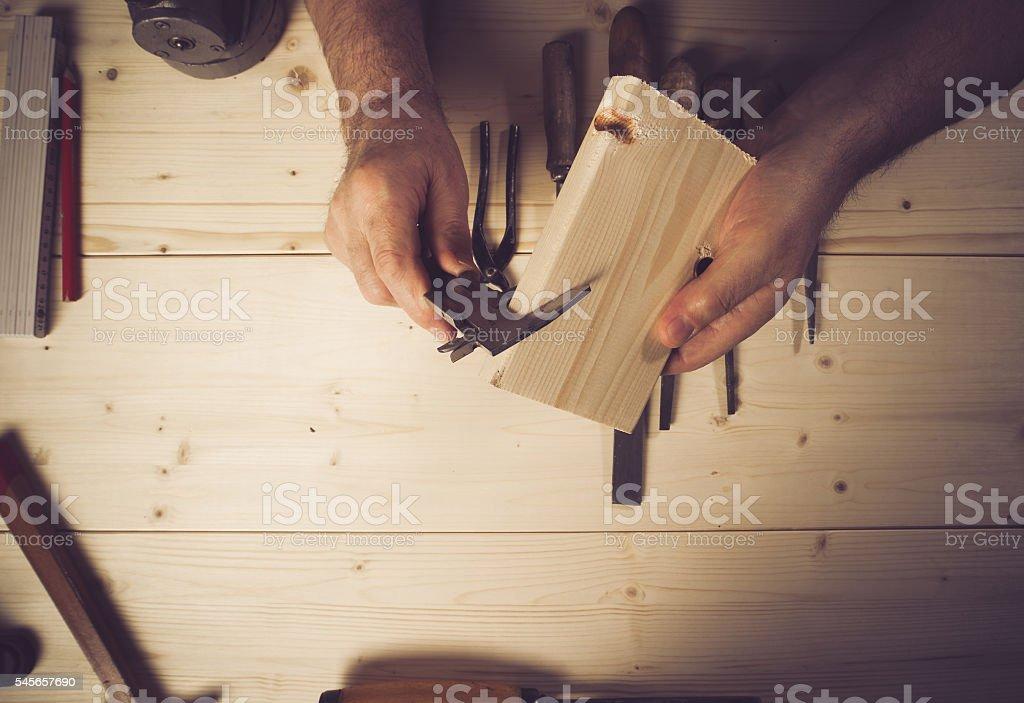 Cropped image of senior carpenter measuring wood in workshop stock photo