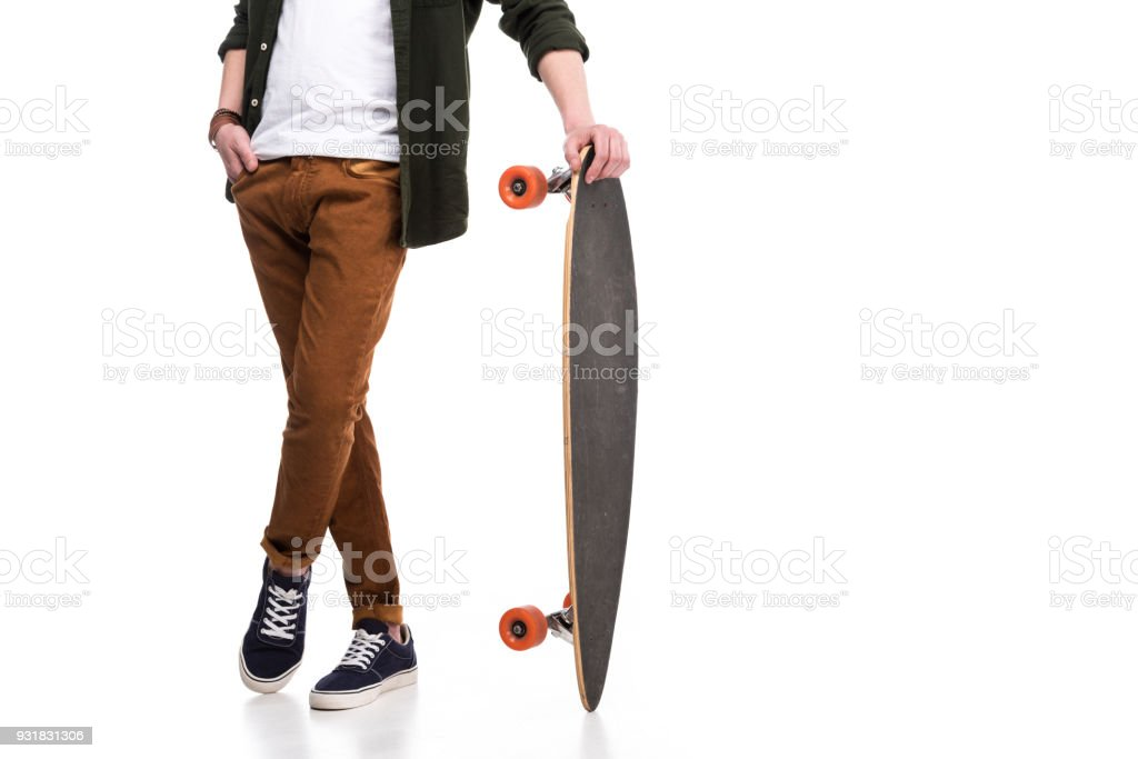 Cropped image of skateboarder standing with longboard on white stock photo