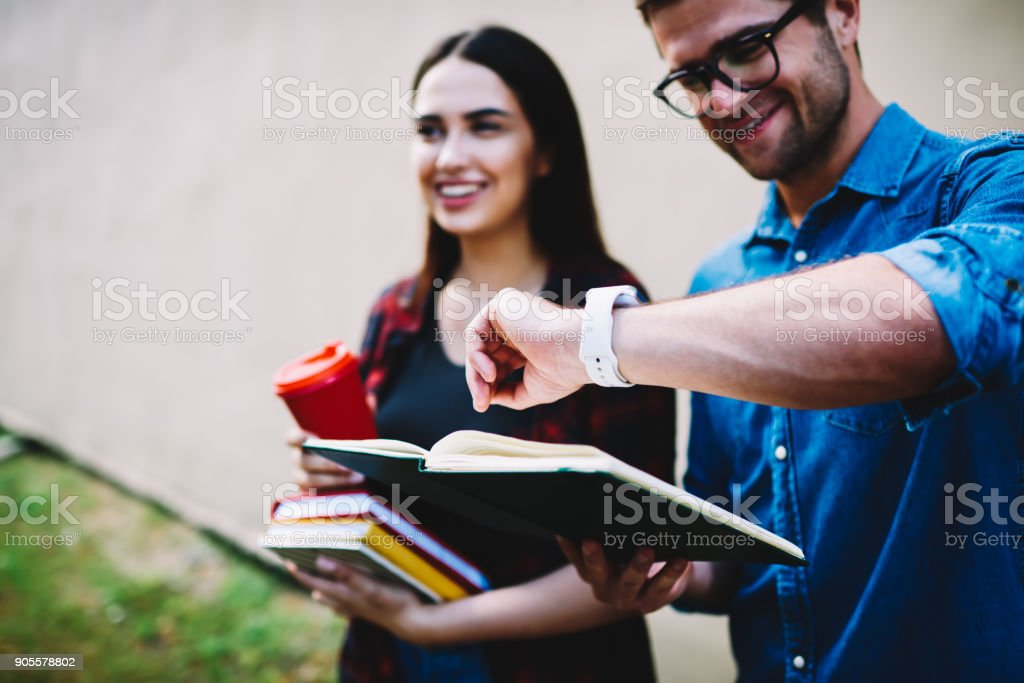 Cropped image of smart cheerful students hurrying to take exams in academy.Selective focus on male hand with wristwatch.Positive hipsters with tasty coffee and training books keeping track of time stock photo