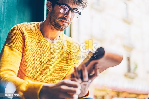1174436608 istock photo Cropped image of smart young man in optical eyegasses reading information from notepad.Pensive hipster guy dressed in yellow sweater learning text from notebook sitting in coworking space 1168817206