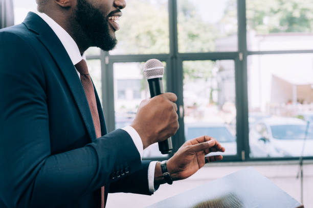 cropped image of smiling african american speaker talking into microphone during seminar in conference hall stock photo