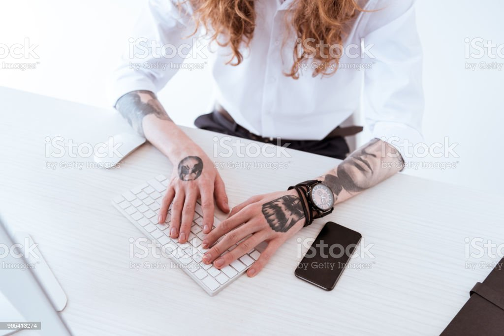 cropped image of stylish businessman with curly hair typing on keyboard zbiór zdjęć royalty-free