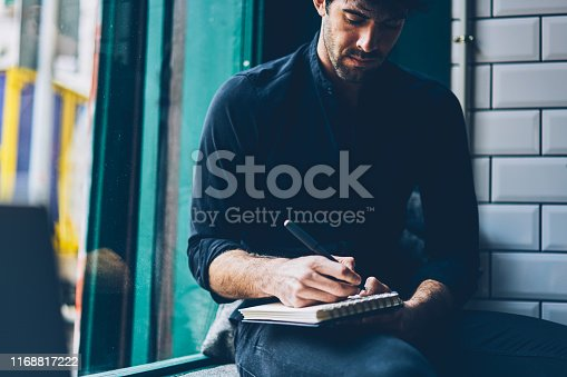 1174436608 istock photo Cropped image of stylish casual dressed young man writing down text information in notepad sitting in coffee shop interior.Pensive student in black shirt noting checklist in notebook 1168817222