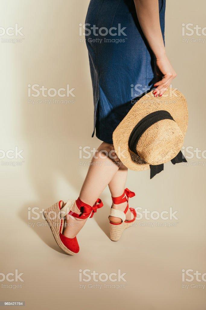 Cropped image d'une femme élégante en sandales à plateforme rouge tenant le chapeau de paille sur fond beige - Photo de A la mode libre de droits