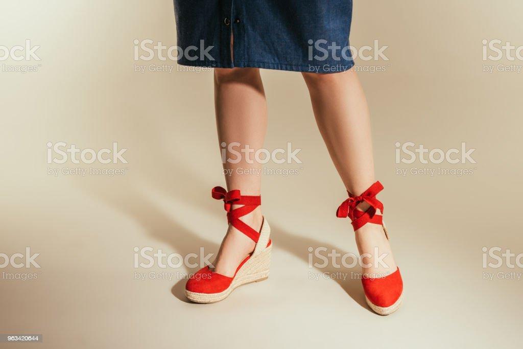 cropped image of stylish woman in red platform sandals on beige background - Zbiór zdjęć royalty-free (Beżowy)