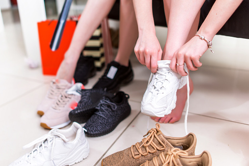 Cropped image of teenage girls trying on sports shoes in a shop