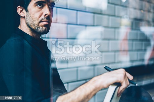 1174436608 istock photo Cropped image of thoughtful young man dressed in black shirt thinking on writing interesting story resting in coworking.Contemplative male pondering on ideas of developig own business project 1168817229