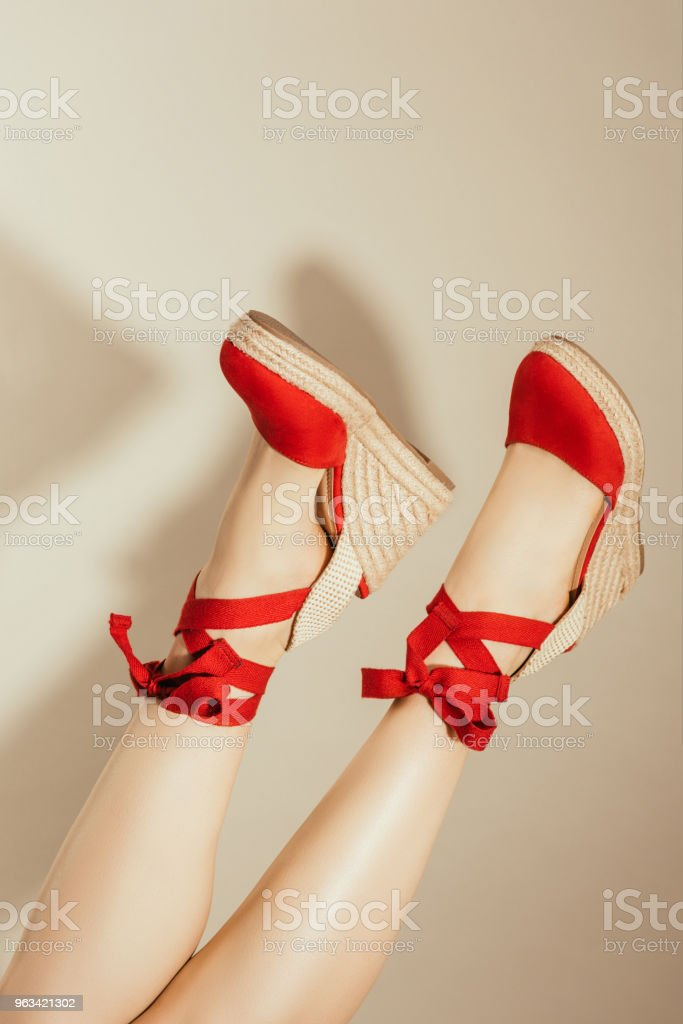 cropped image of upside down female feet in stylish red platform sandals on beige background - Zbiór zdjęć royalty-free (Beżowy)