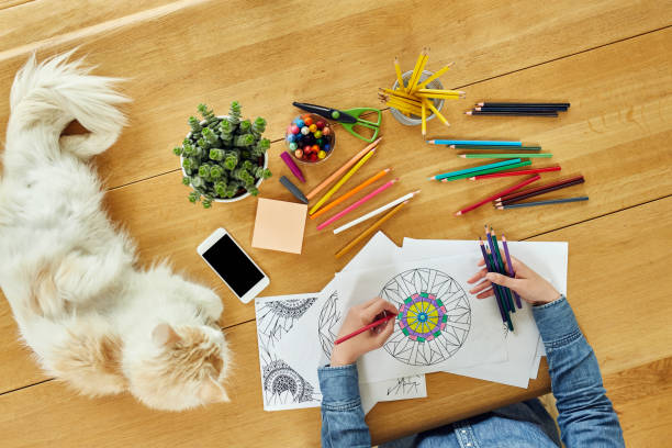 cropped image of woman coloring design by cat on table - katze zeichnen stock-fotos und bilder