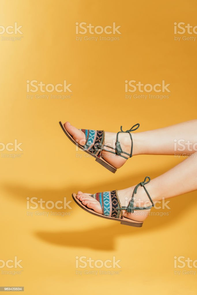 cropped image of woman feet in stylish sandals on yellow background - Zbiór zdjęć royalty-free (Cięcie w lini dolnej)