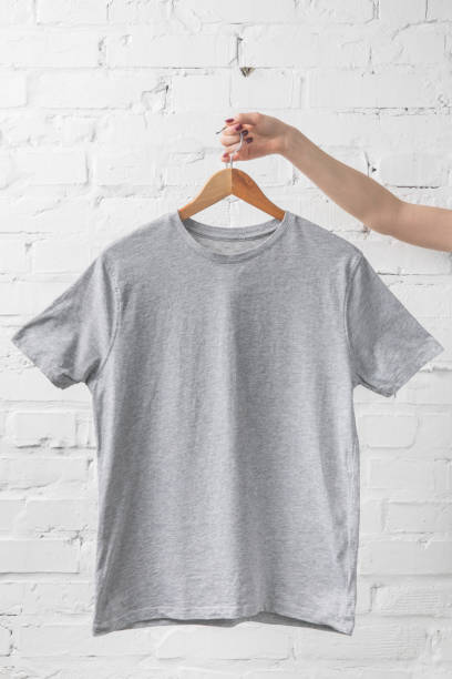 cropped image of woman holding grey shirt on hanger cropped image of woman holding grey shirt on hanger coathanger stock pictures, royalty-free photos & images