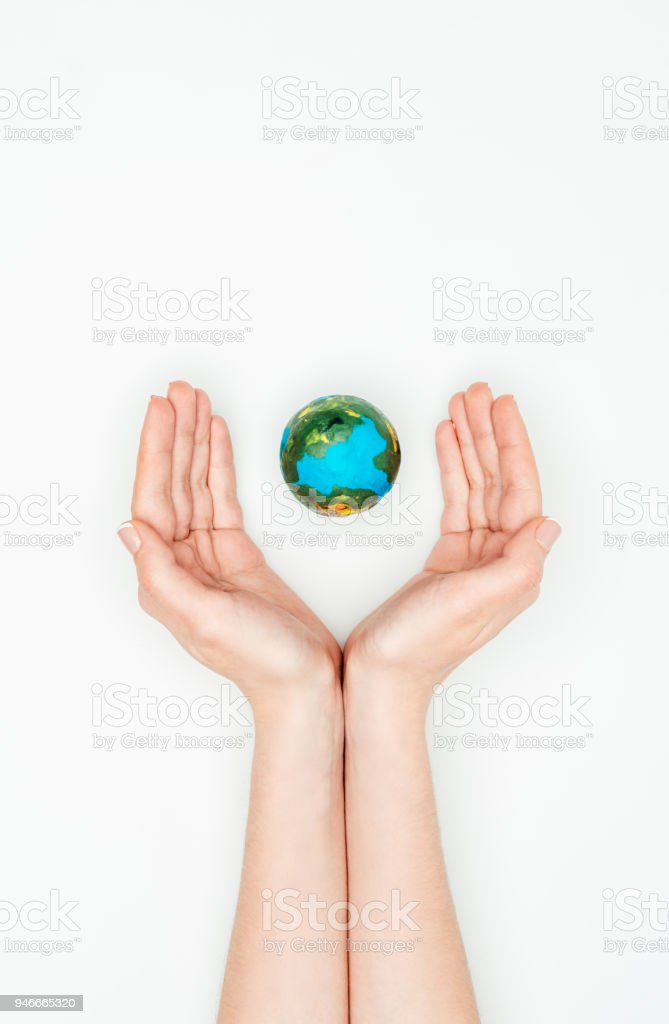 cropped image of woman holding hands around earth model isolated on white, earth day concept stock photo