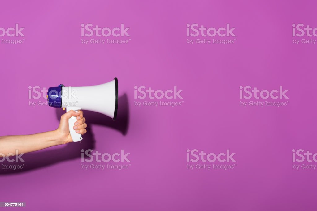 cropped image of woman holding megaphone on purple background stock photo