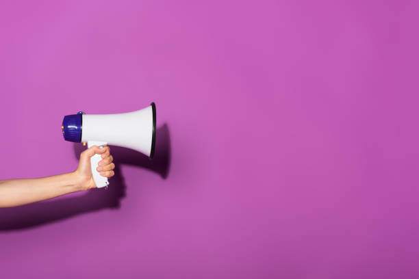 cropped image of woman holding megaphone on purple background - violet stock photos and pictures
