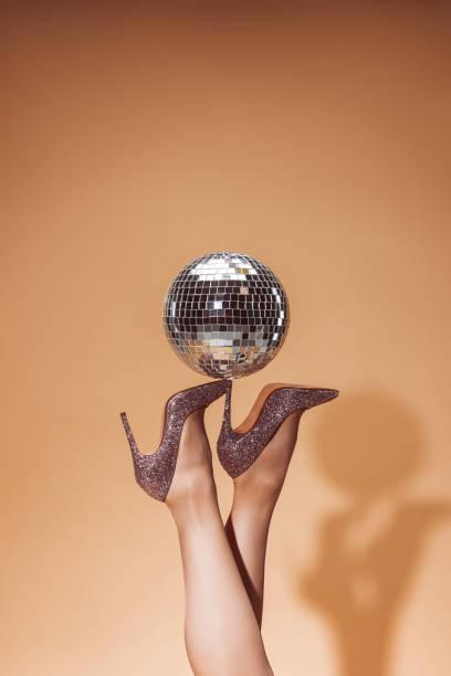 beschnitten, bild frau mit glänzenden disco-kugel auf high heels auf party auf beige - glitzer absätze stock-fotos und bilder