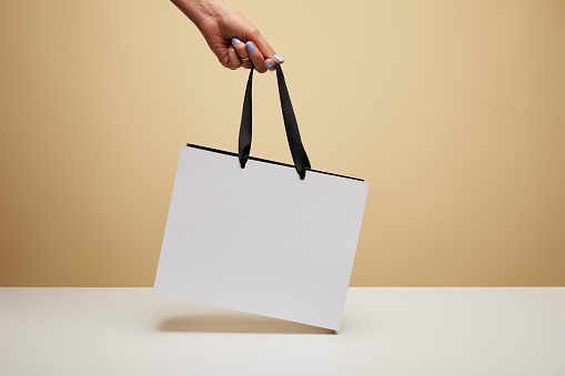 cropped image of woman holding white shopping bag above white table isolated on beige