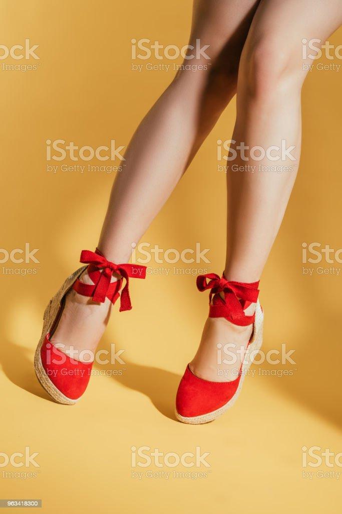 cropped image of woman legs in stylish platform sandals on yellow background - Zbiór zdjęć royalty-free (Cięcie w lini dolnej)