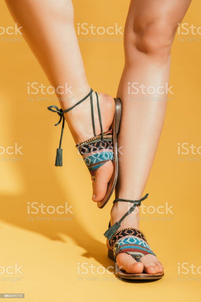 Cropped image de jambes de femme en sandales élégantes sur fond jaune - Photo de A la mode libre de droits