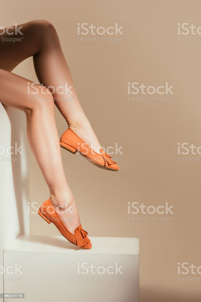 cropped image of woman legs in stylish slipper shoes on beige background - Zbiór zdjęć royalty-free (Beżowy)