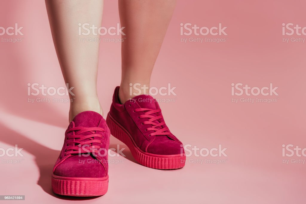 cropped image of woman legs in stylish sneakers on pink background - Zbiór zdjęć royalty-free (But sportowy)