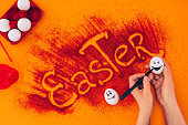 istock cropped image of woman painting smileys on easter eggs on orange 928894666