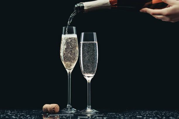 zugeschnittenes bild frau gießt champagner aus der flasche in die gläser auf schwarz - sektglas stock-fotos und bilder