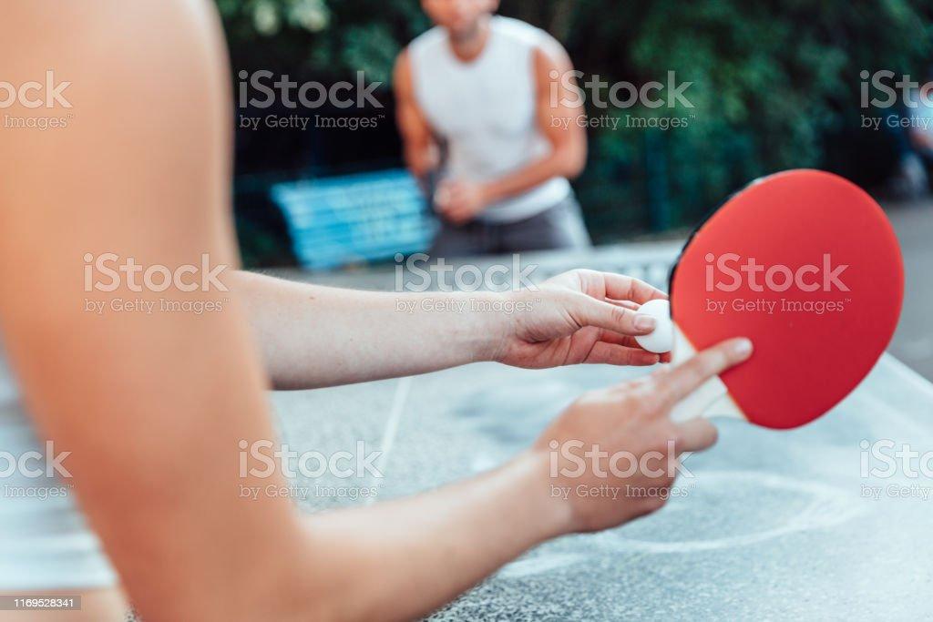 Abgeschnittenes Bild von Frau, die Ball auf Tischtennis serviert, während sie mit mann spielt - Lizenzfrei Aufschlagen - Sport Stock-Foto