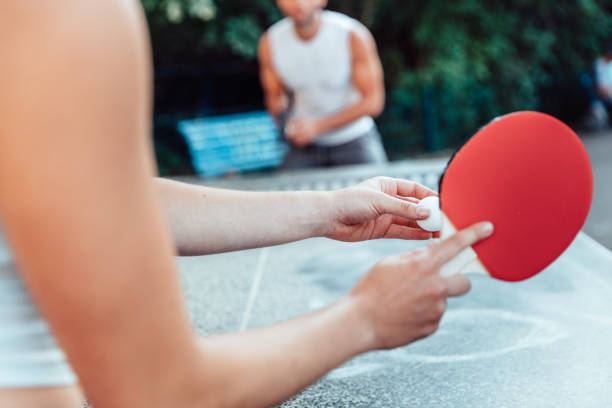 Cropped image of woman serving ball on table tennis while playing with man stock photo