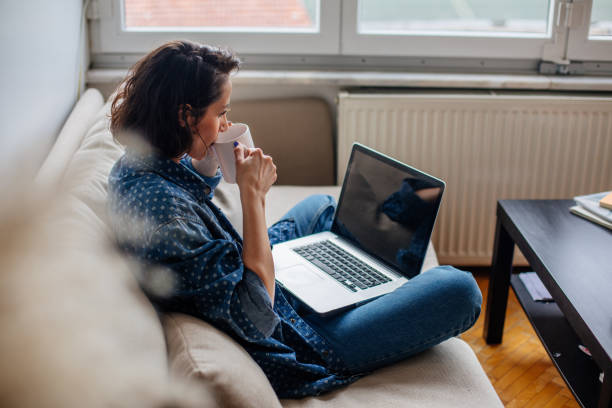 Cropped image of woman using laptop with blank screen Cropped image of woman using laptop with blank screen looking over shoulder stock pictures, royalty-free photos & images