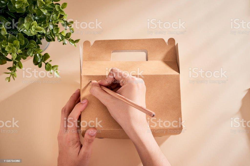 Cropped image of woman writing best wishes on box with present stock photo