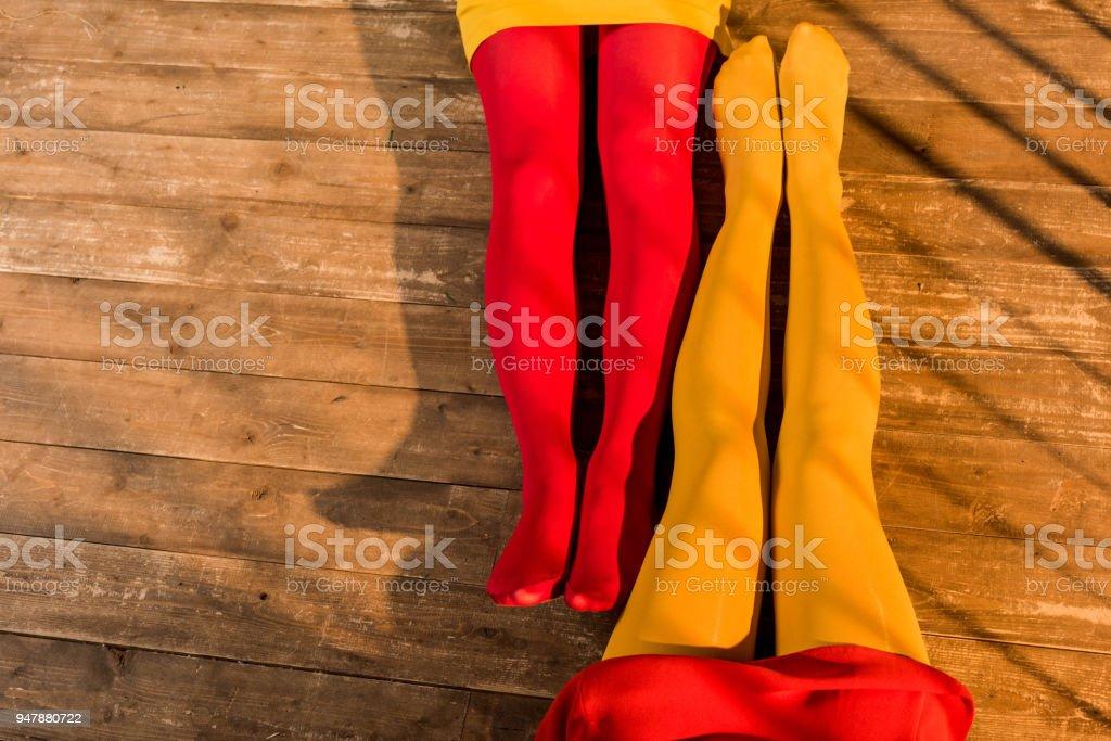 570ccc058 imagem recortada de mulheres de meia-calça colorida e vestido sentada no  chão em casa